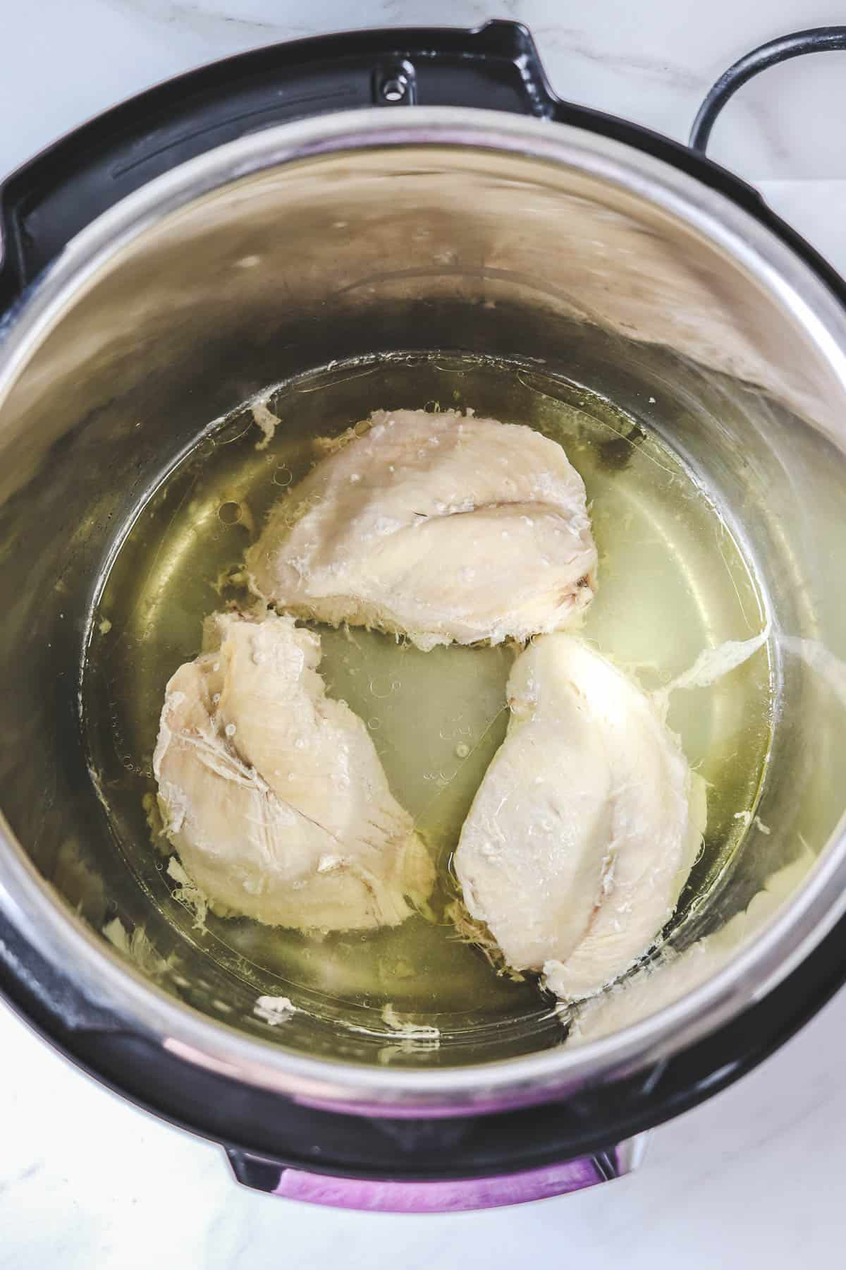 cooked chicken breasts in broth in the instant pot