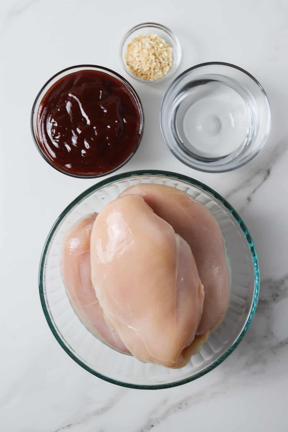 ingredients in instant pot barbeque chicken - chicken breasts, water, bbq sauce, and dry minced onion