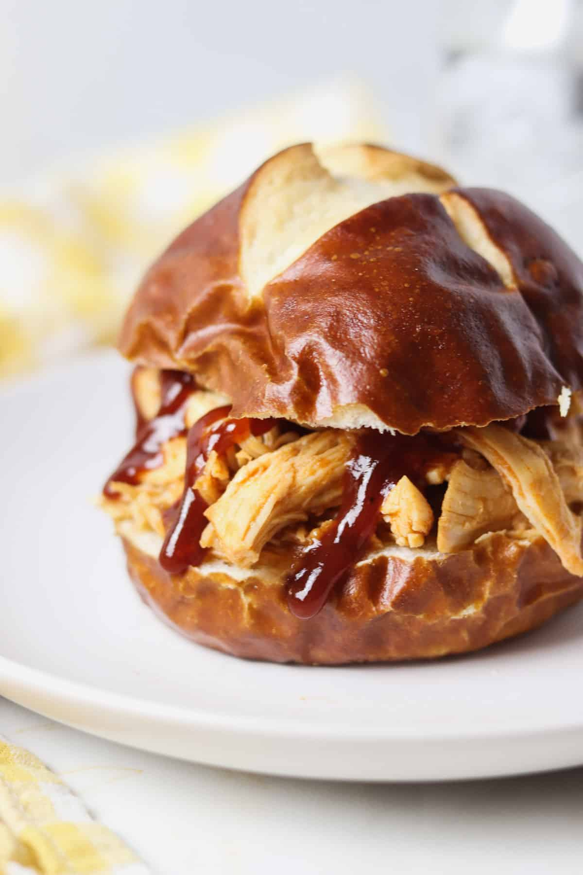 shredded bbq chicken on a pretzel bun