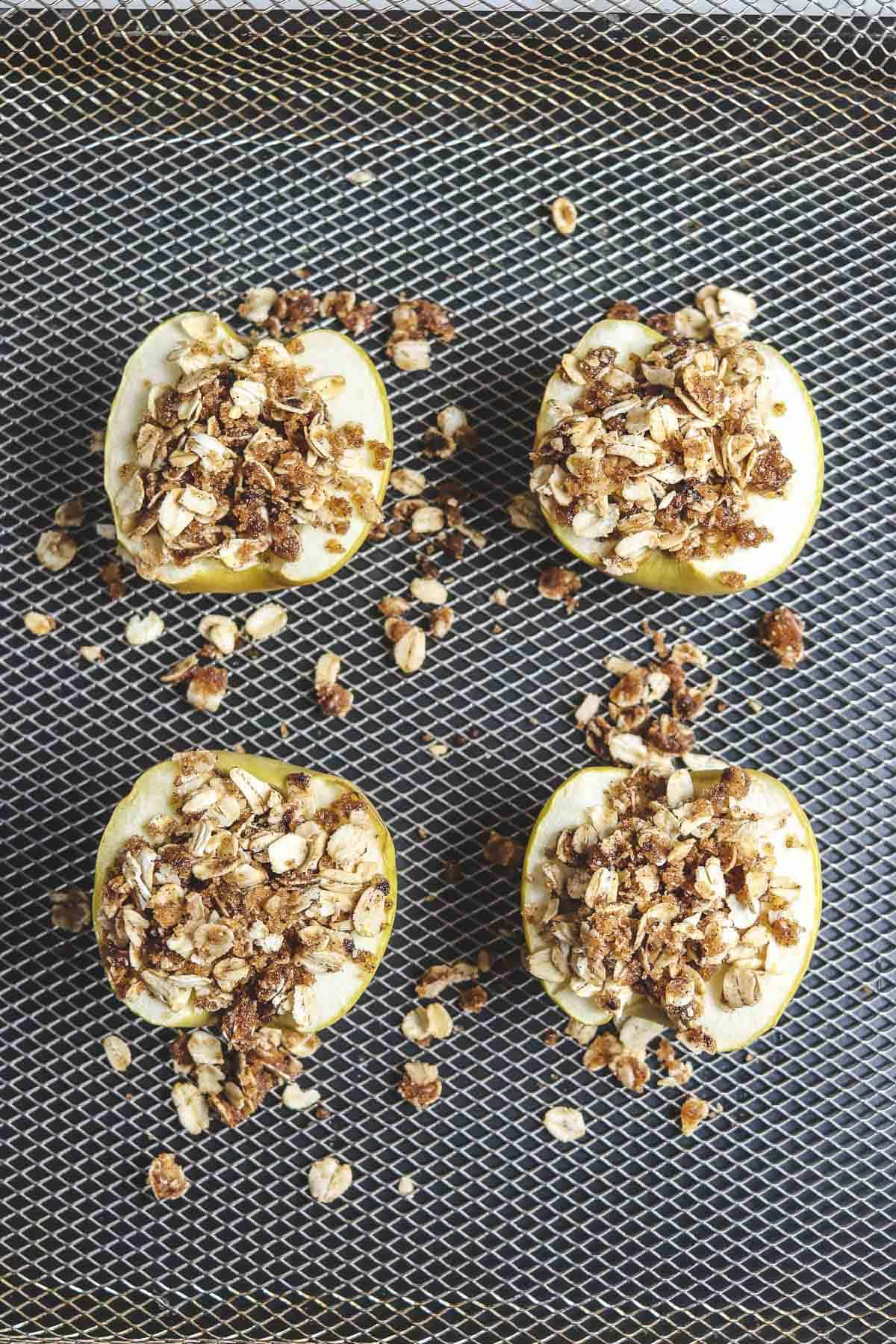 apple halves topped with oat topping in air fryer basket