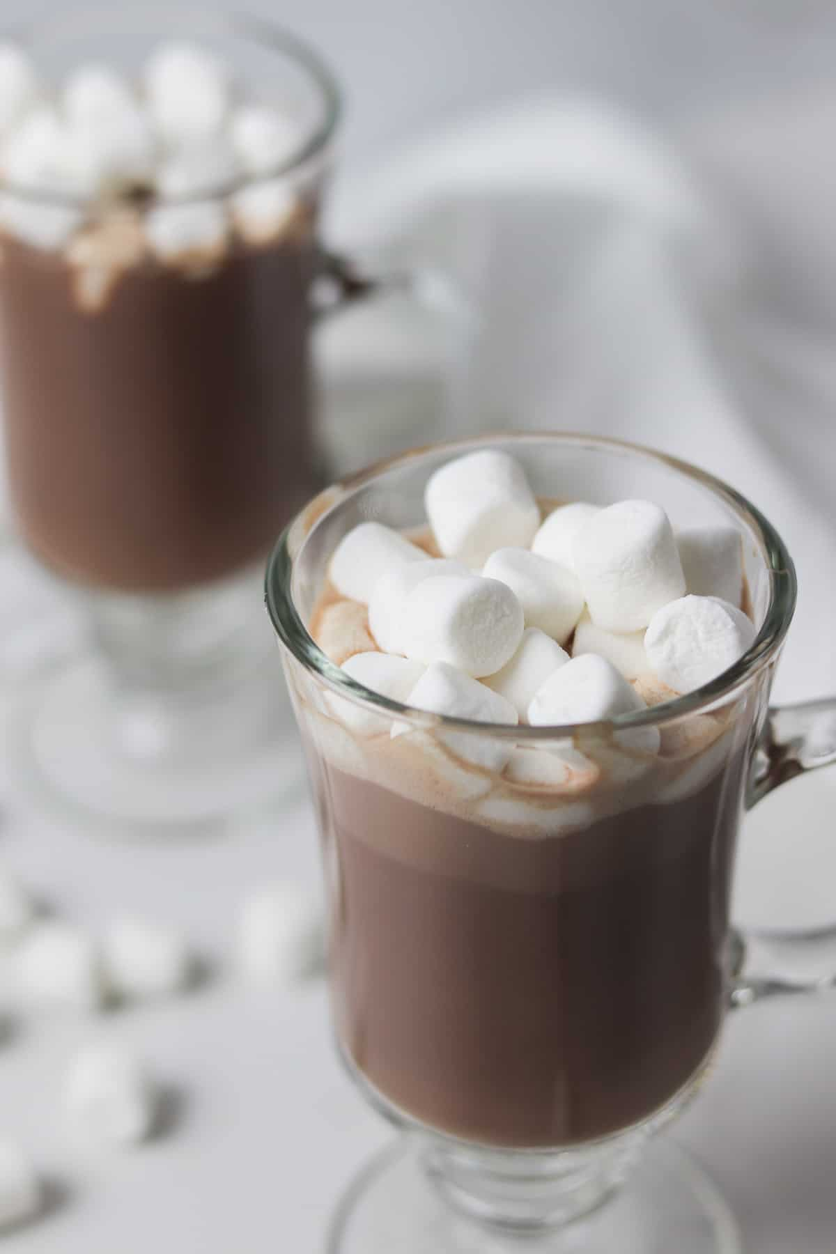 two glasses of hot chocolate topped with marshmallows