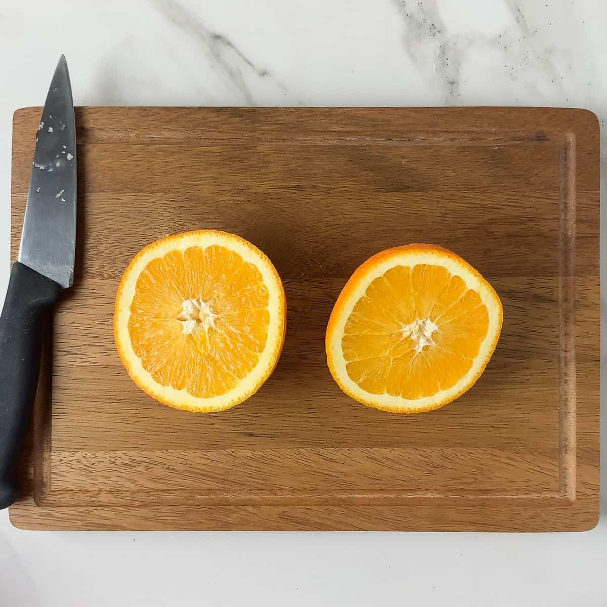 navel oranges sliced in half on wood cutting board