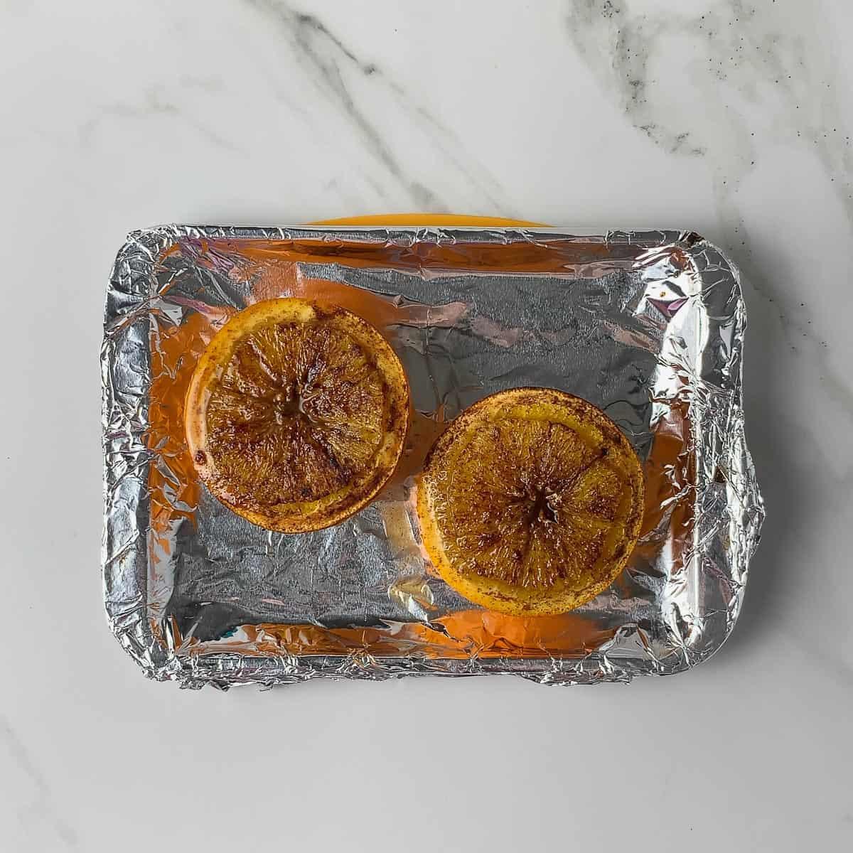 cooked baked oranges on baking sheet