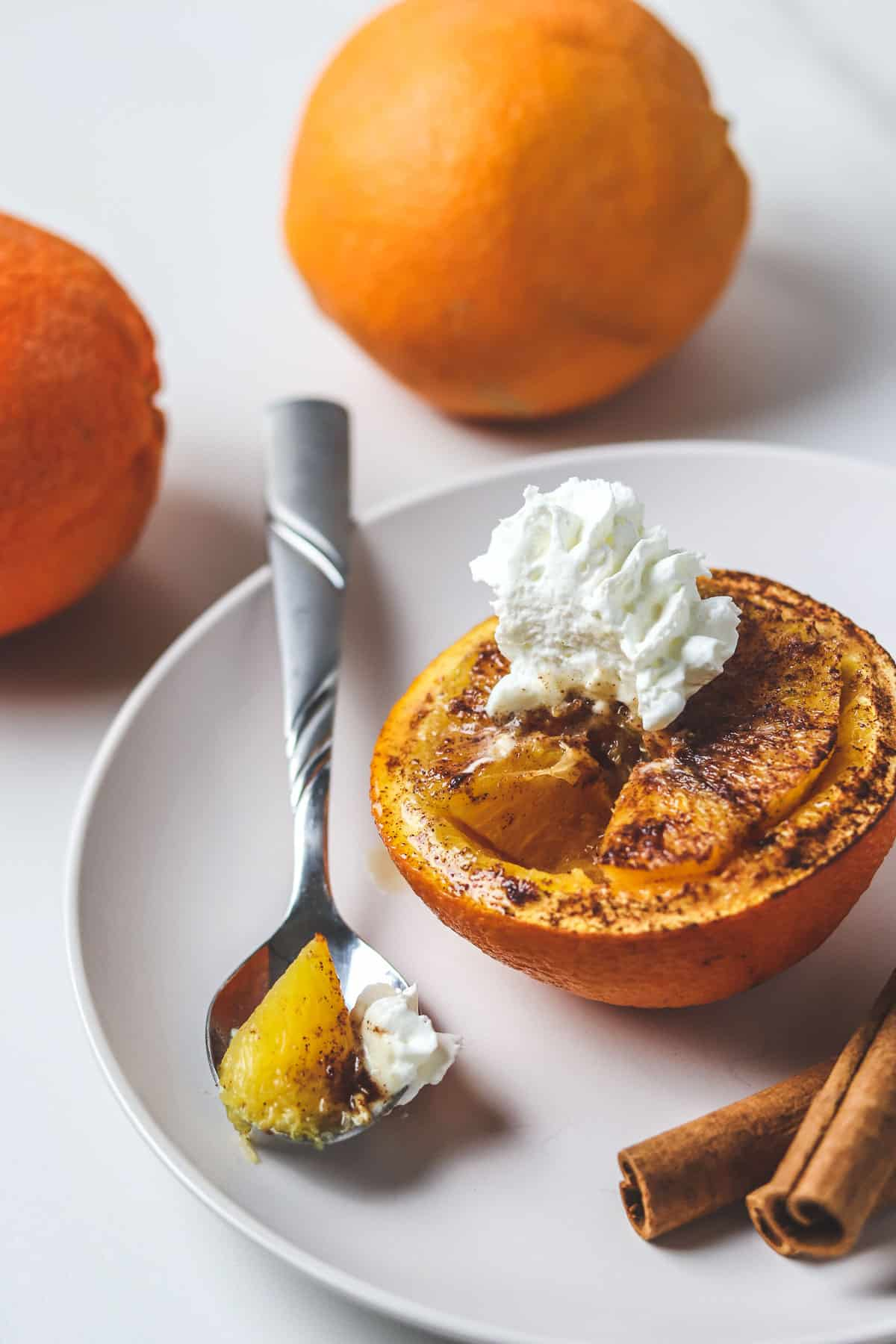 baked orange topped with whipped cream