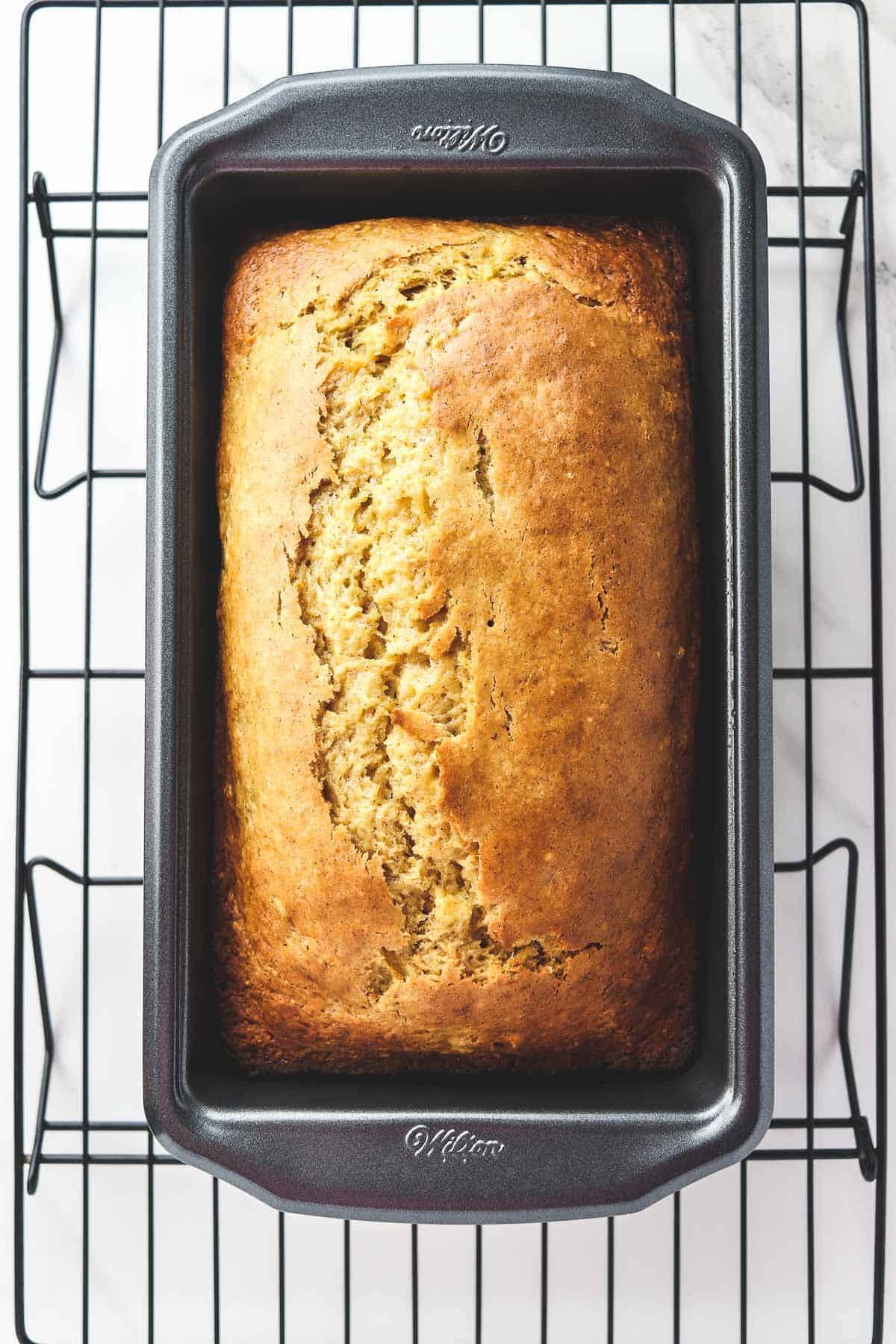 cooked banana bread cooling in a loaf pan