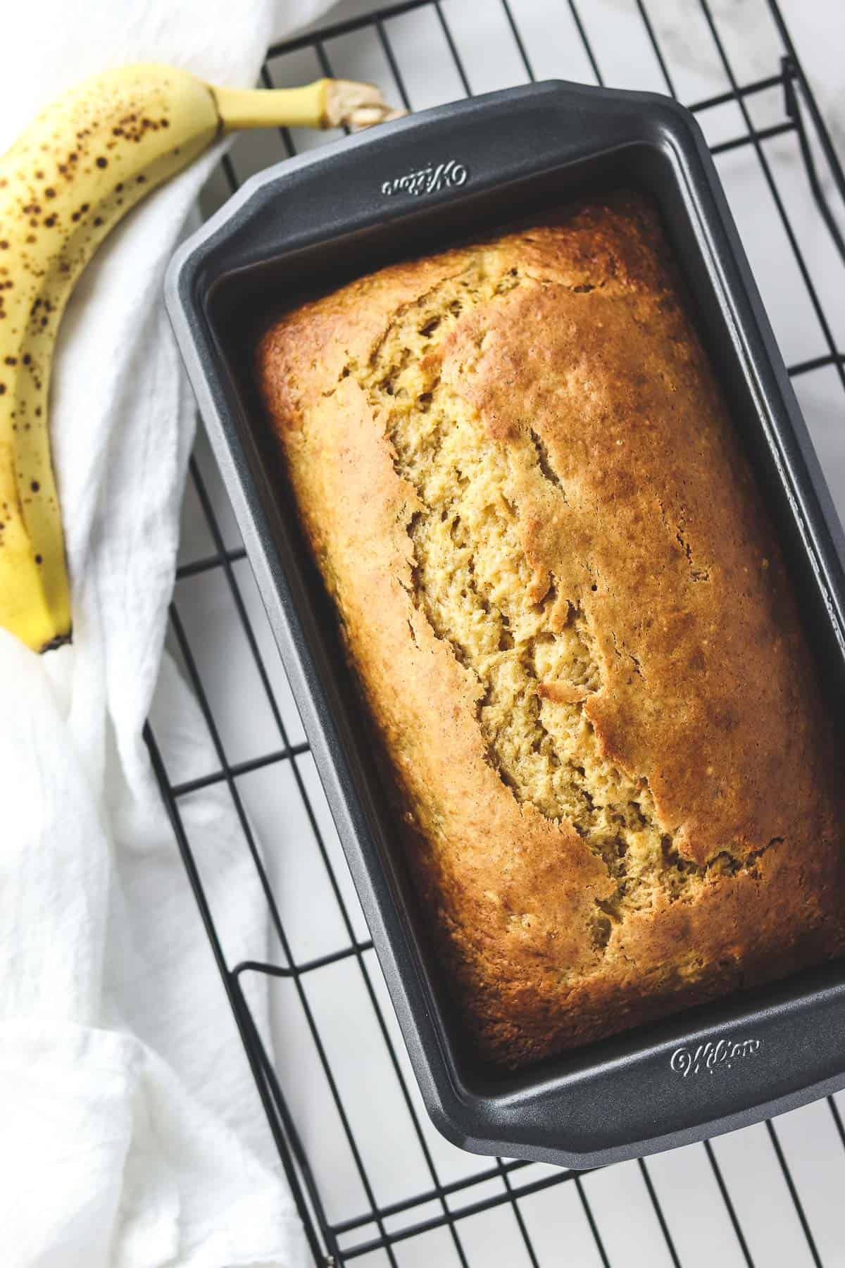 healthy banana bread in a loaf pan with a ripe banana