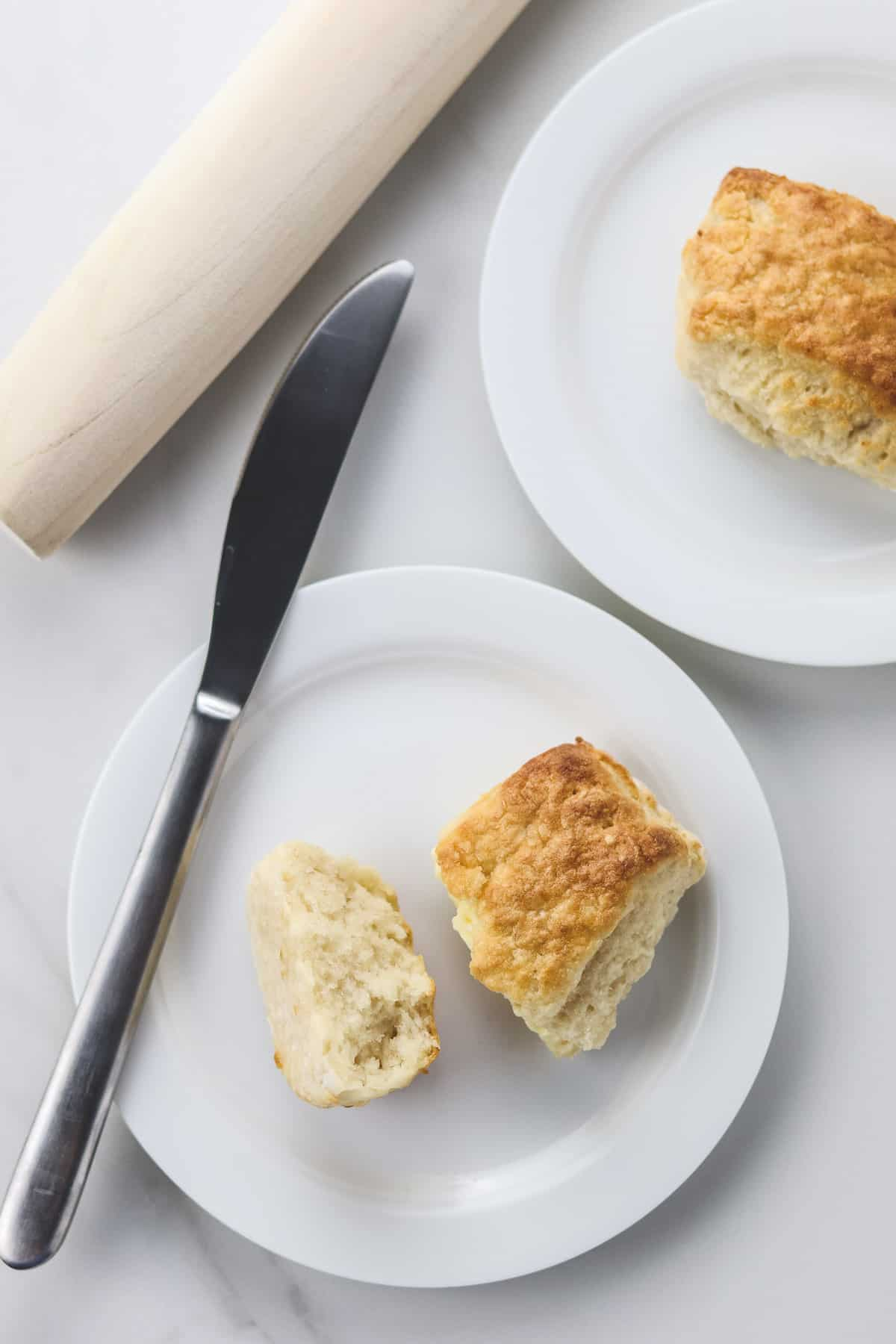 healthy air fryer biscuits on white plates with a butter knife