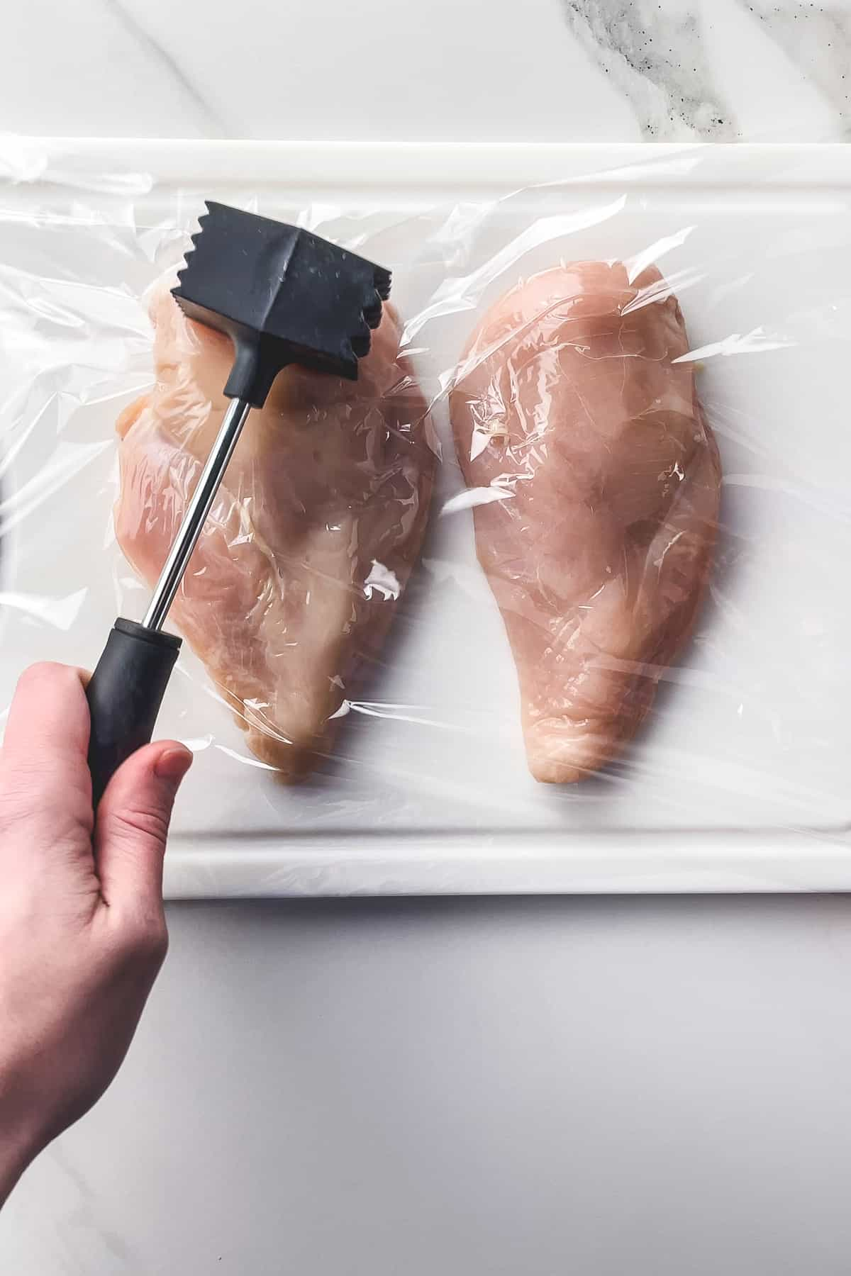 pounding chicken breasts on a cutting board