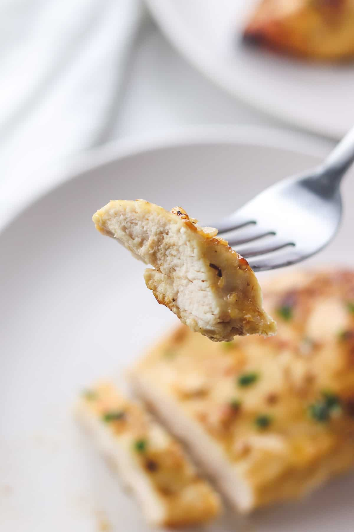 taking a bite of chicken breast with a fork