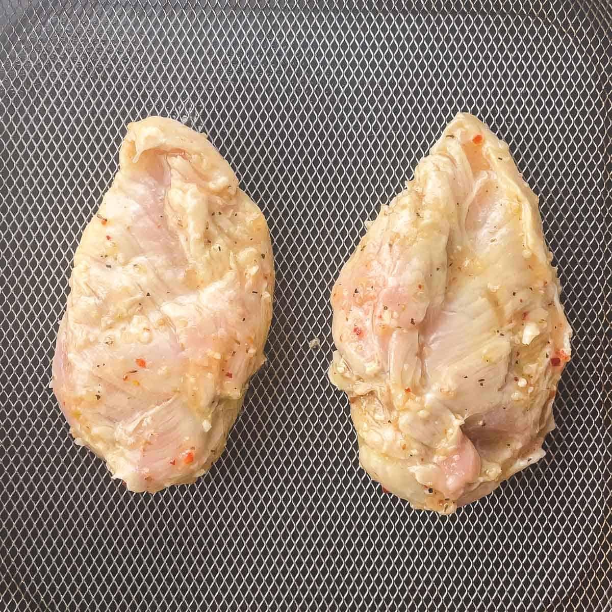 raw chicken breasts in air fryer basket
