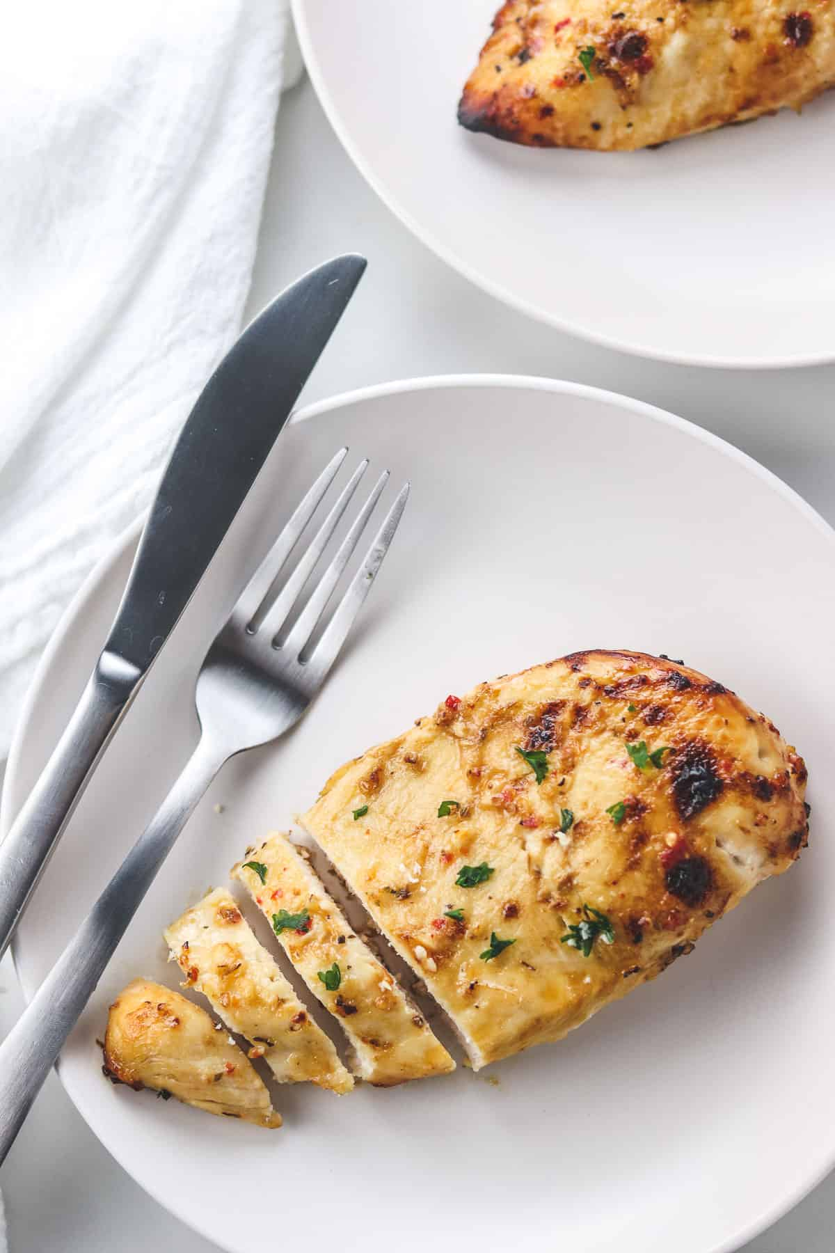 cut chicken breast on a white plate with a fork and knife