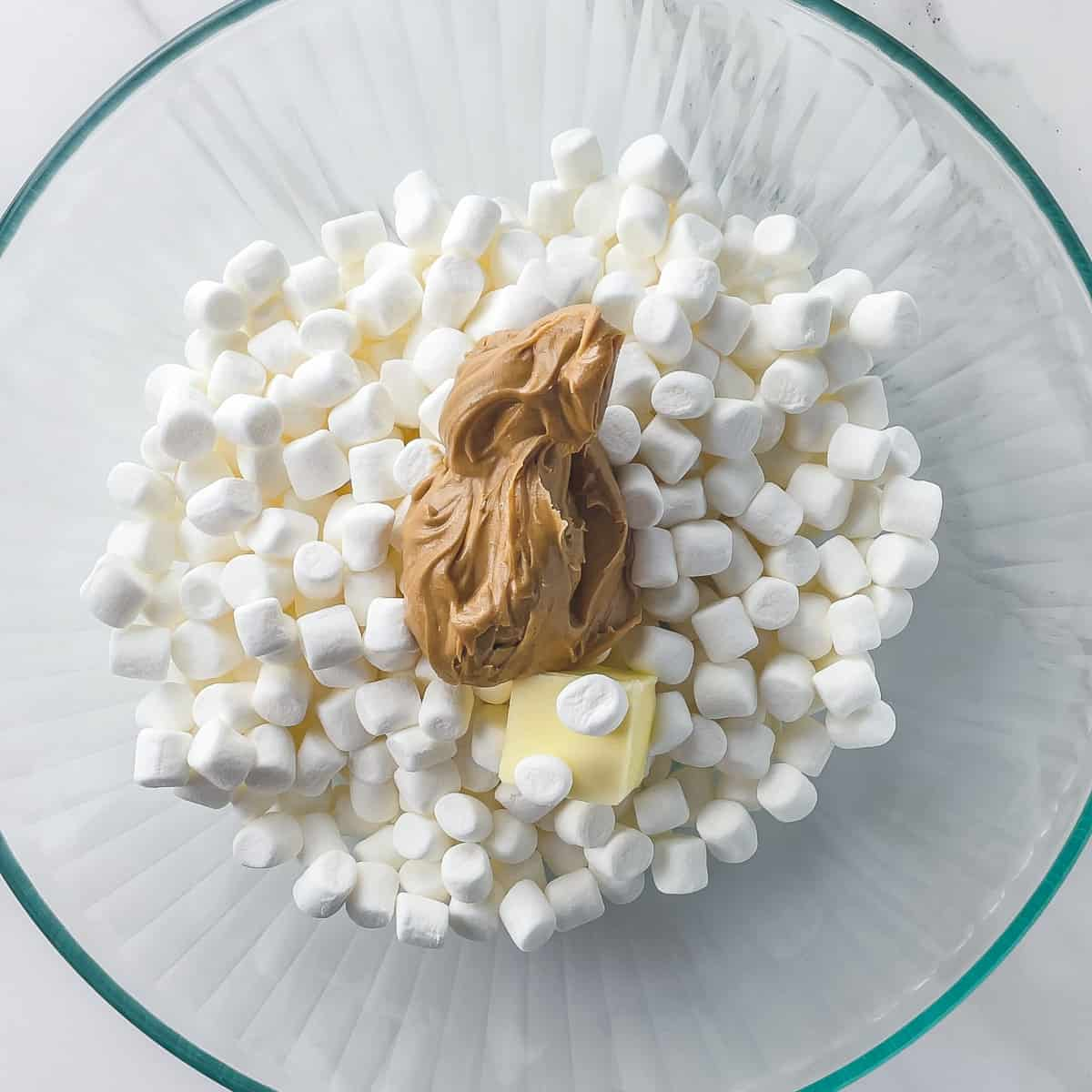 marshmallows, peanut butter, and butter in a glass mixing bowl