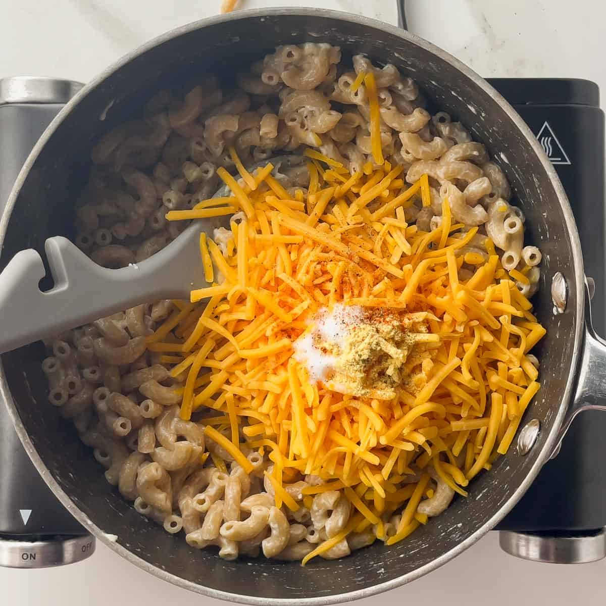 ingredients for cheese sauce tossed into the pot of noodles