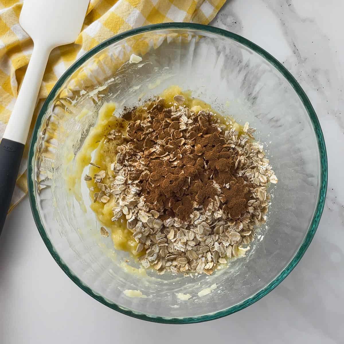 mashed banana, oatmeal, and cinnamon in mixing bowl