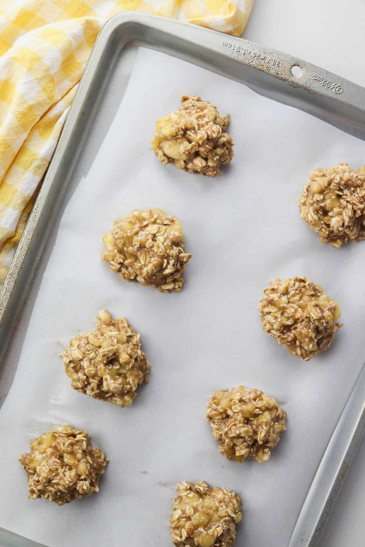 banana oatmeal cookies on a cookie sheet with yellow towel