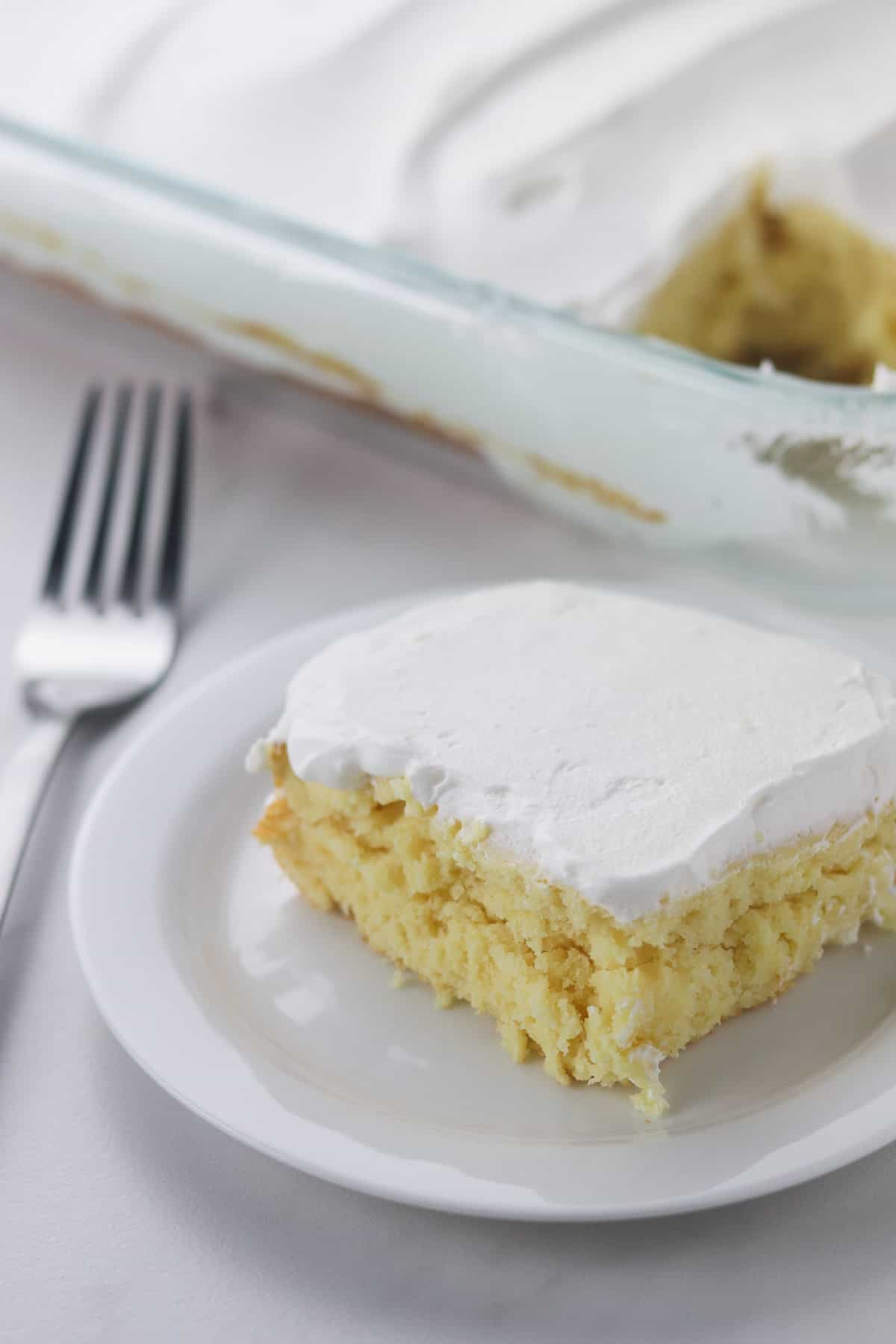 a piece of light yogurt cake on a white plate with a fork
