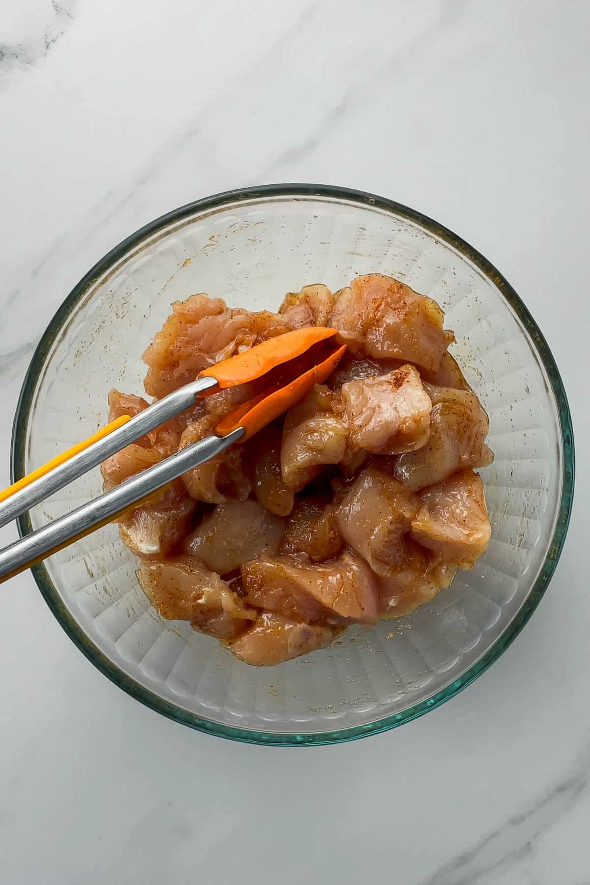 raw chicken mixed with rotisserie seasonings in a glass mixing bowl